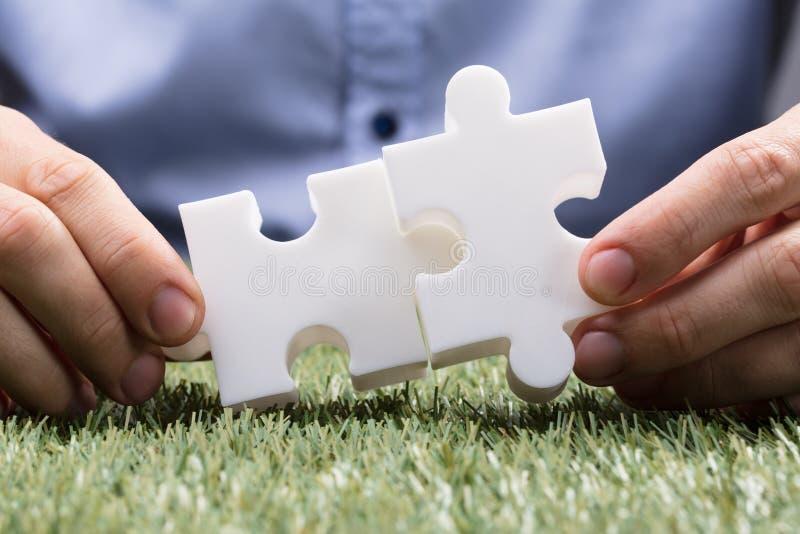 Puzzle di Person Connecting Two White Jigsaw immagine stock libera da diritti