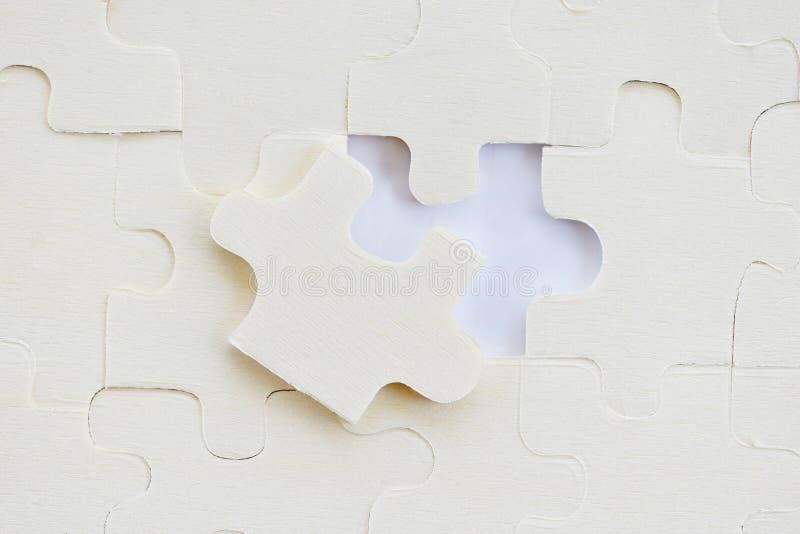 Puzzle di puzzle sui pezzi bianchi di /Jigsaw su struttura fotografie stock