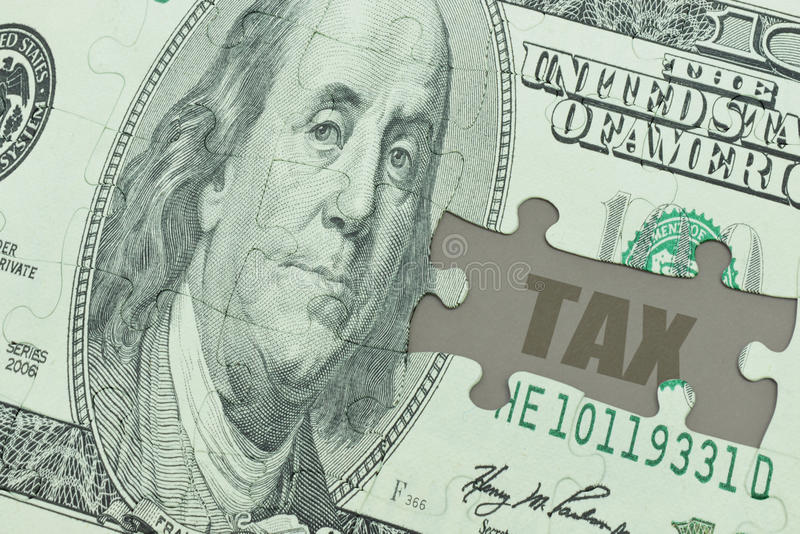 Puzzle with the dollar banknote and the text tax. stock photo