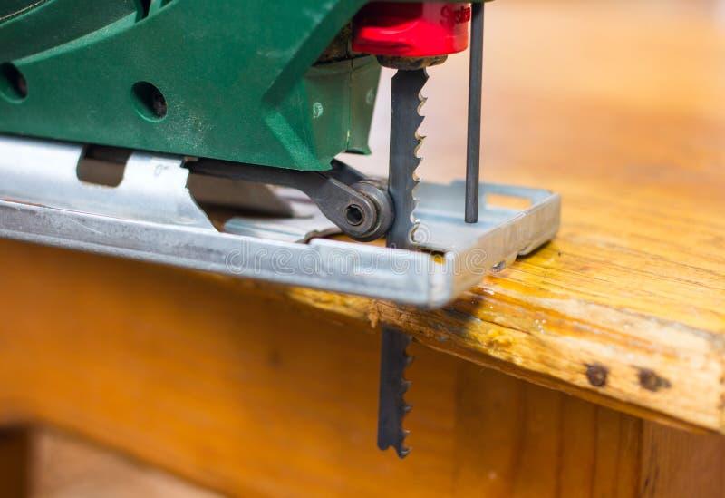 Puzzle elettrico che taglia un pezzo di legno fotografia stock