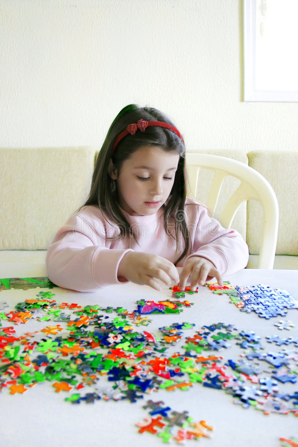Puzzle game. Little six year old girl alone at home, deeply concentrated on solving a puzzle royalty free stock photo
