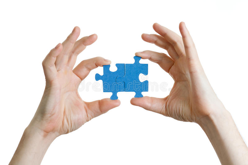 Puzzle in hands on white background royalty free stock photography