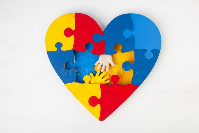 Puzzle heart hands support autism awareness. Puzzle heart hands on white wooden background support autism awareness royalty free stock image