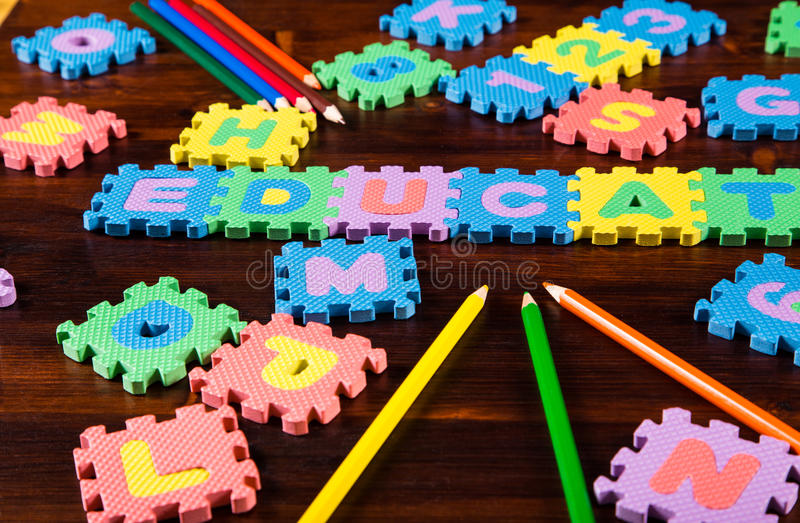 Puzzle letters with pencils on wooden background royalty free stock photo