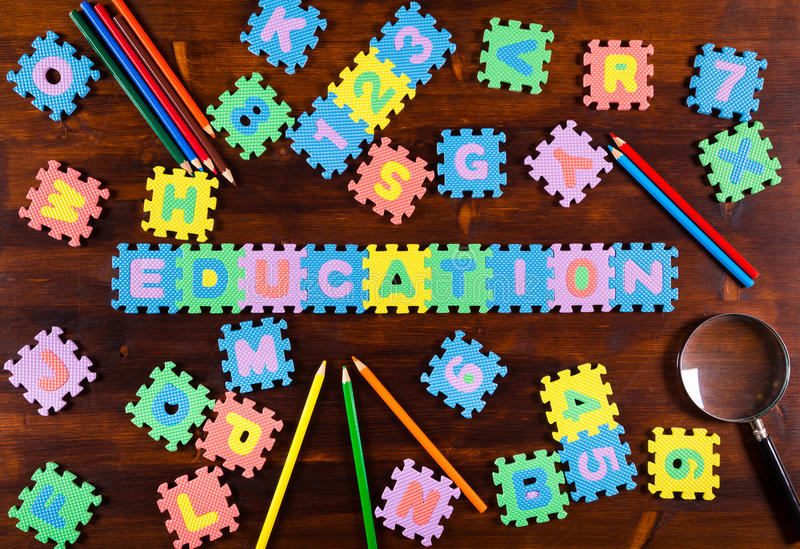 Puzzle letters with pencils on wooden background royalty free stock photos