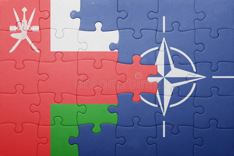 Puzzle with the national flag of oman and nato royalty free stock image