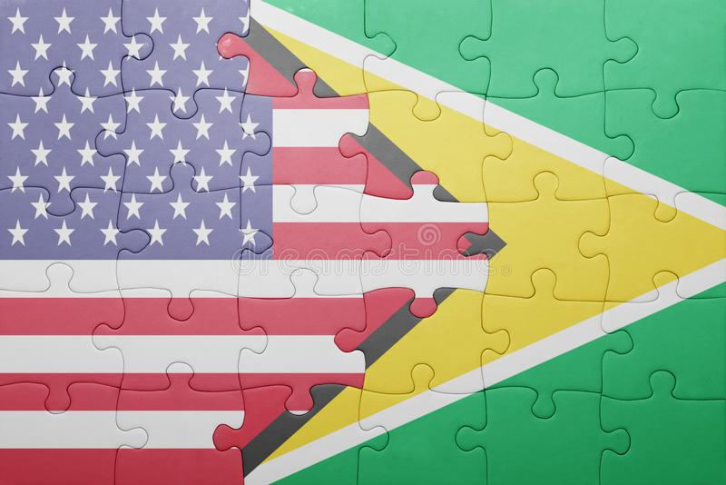 Puzzle with the national flag of united states of america and guyana. Concept royalty free stock photo