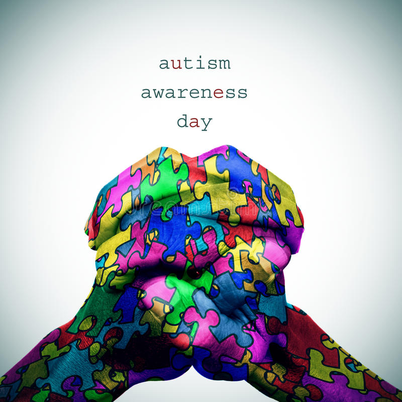 Puzzle-patterned hands and text autism awareness day vector illustration