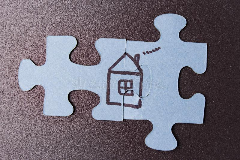 Puzzle with picture of house on black background. The concept of home and family. Insurance and house building. royalty free stock photo