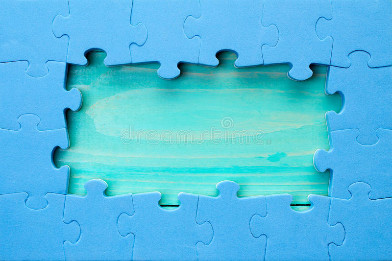 Puzzle pieces arranged as a border around a green wooden surface stock photography