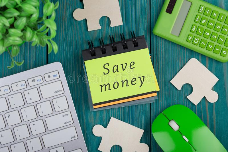 Puzzle pieces, calculator, note pad with text & x22;Save money& x22;, computer keyboard royalty free stock photos