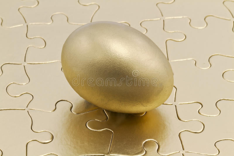 Puzzle pieces with gold nest egg royalty free stock photography