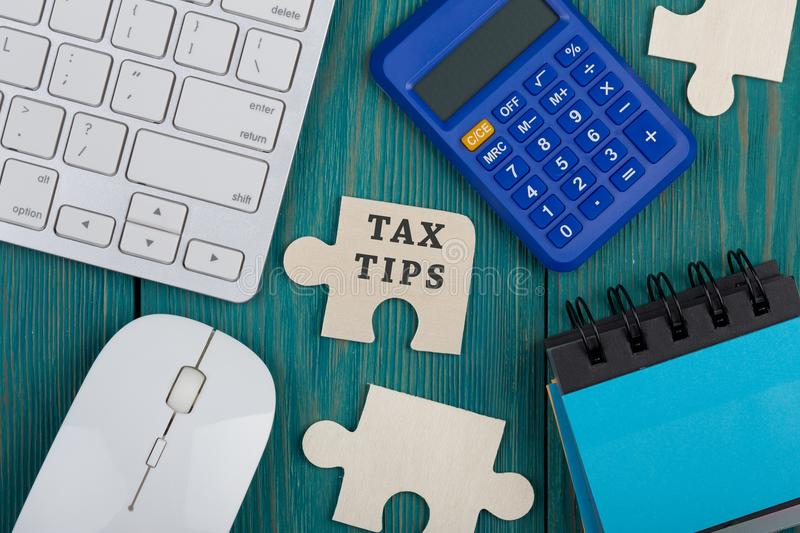 Puzzle pieces with text & x22;Tax tips& x22;, calculator, note pad, computer keyboard. And mouse on a blue wooden background royalty free stock photos
