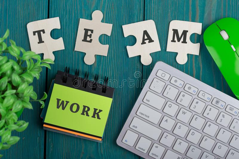 Puzzle pieces with text & x22;team& x22;, note pad with word & x22;work& x22;, computer keyboard stock photo