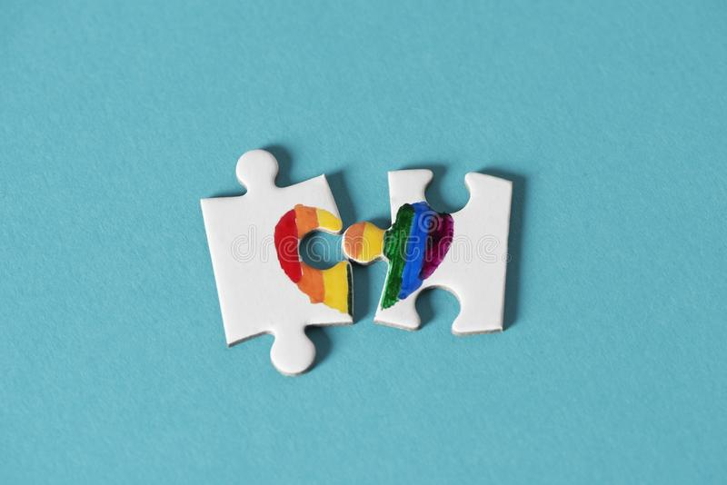 Puzzle pieces about to form a rainbow heart. Two pieces of a puzzle, which put together form a rainbow heart, on a blue background, depicting the lack of right stock photo