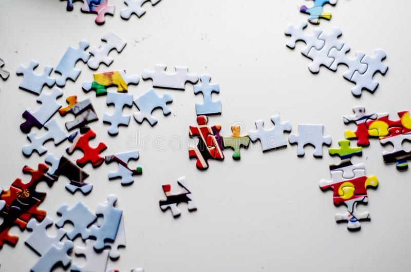 Puzzle pieces white table. Small puzzle pieces on a white table royalty free stock images