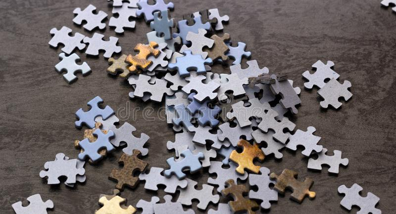 Puzzle pieces on a wooden surface, closeup, top view. royalty free stock photo