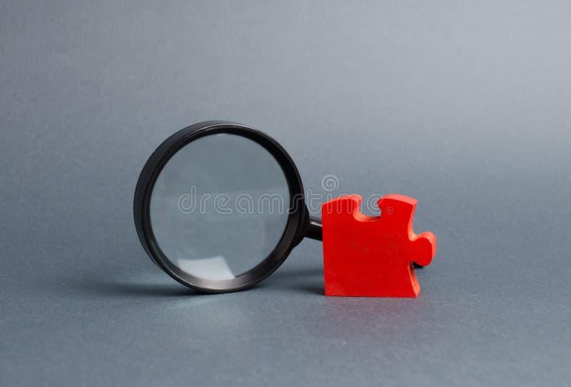 Puzzle rouge et loupe Le concept de trouver le détail ou l'élément absent dans la vue d'ensemble ou la stratégie Business images stock