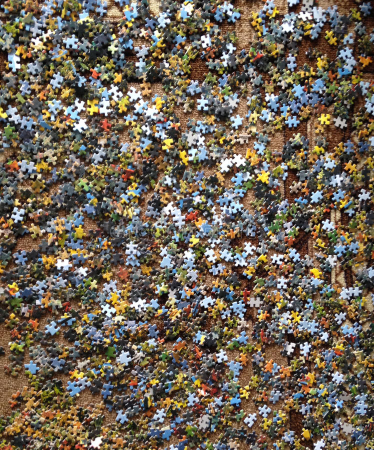 Puzzle scattered on a brown floor royalty free stock photography