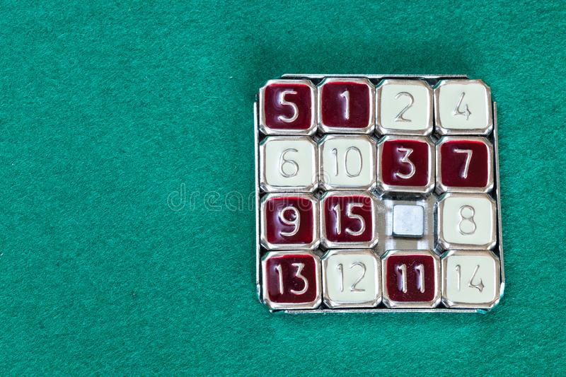 15-puzzle sliding puzzle game on green table. Top view of 15-puzzle magic 15 sliding puzzle game on green baize table with copyspace stock photos