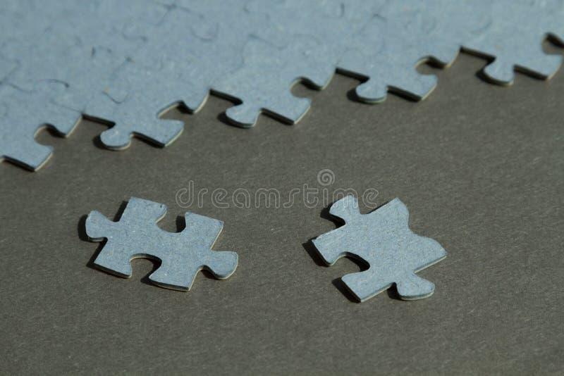 Puzzle su fondo nero con due pezzi da  fotografia stock