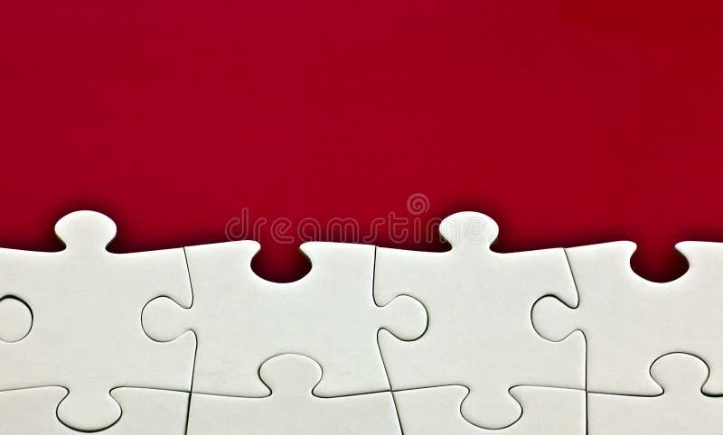 Puzzle su fondo rosso fotografia stock libera da diritti