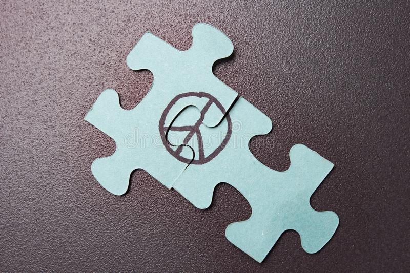 Puzzle with symbol of pacifism on black background. Concept of the world. World Day of Peace. Sign of Peace. stock images