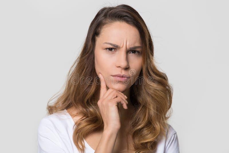Puzzled使有在演播室墙壁上隔绝的皱眉的面孔的妇女为难 库存照片