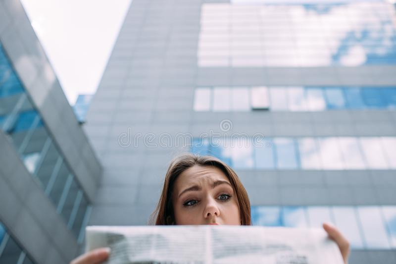 Puzzled смутило озадаченную газету чтения женщины стоковое изображение rf