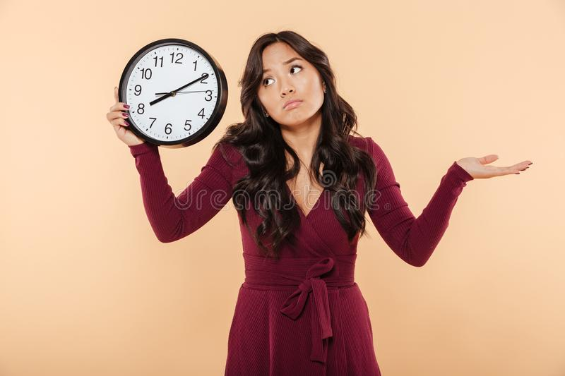 Puzzled brunette woman with curly long hair holding clock showing time after 8 gesturing like she is late or do not care over pea. Puzzled brunette woman with stock image