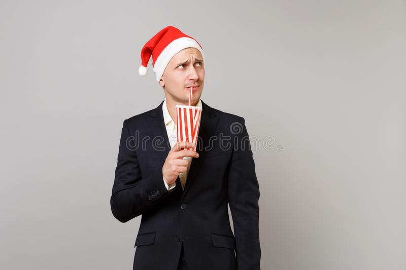 Puzzled business man in Christmas hat looking up, drinking soda from plastic cup isolated on grey background. Achievement career wealth business. Happy New royalty free stock photography
