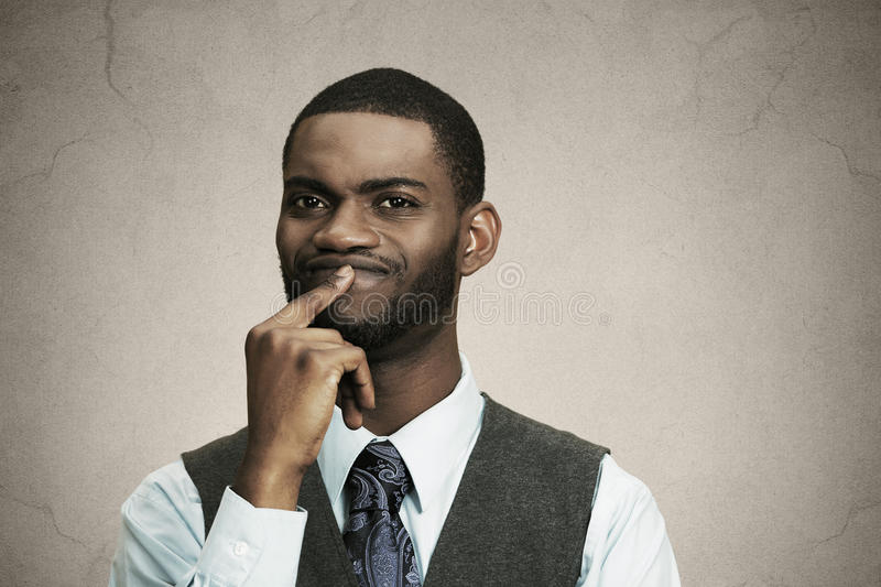 Puzzled business man thinking. Closeup portrait young puzzled business man thinking deciding deeply about something finger on lips looking confused isolated royalty free stock image