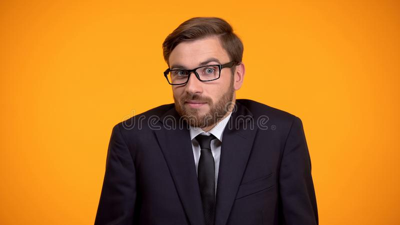 Puzzled businessman shrugging shoulders, trying to make hard decision, choice. Stock photo royalty free stock image