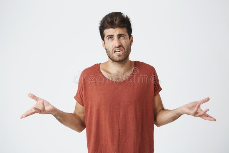 Puzzled and clueless bearded man with stylish hairstyle dressed in casual clothing shrugging shoulders and staring at. Camera with confused look after he made royalty free stock photo