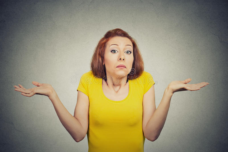 Puzzled clueless woman shrugs shoulders royalty free stock photography