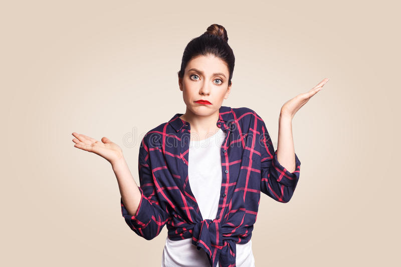 Puzzled and clueless young woman with arms out, shrugging her shoulders, saying: who cares, so what, I don`t know. stock photos