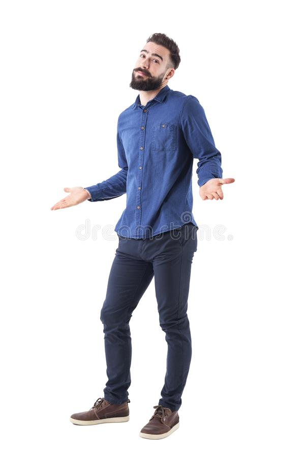 Puzzled confused man in blue shirt shrugging shoulders looking at camera. Full body isolated on white background royalty free stock photo