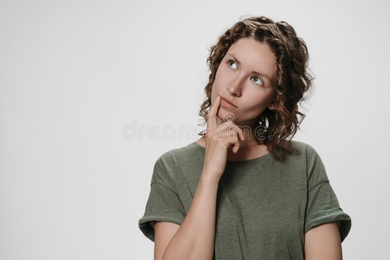 Puzzled curly woman holds chin, looks thoughtfully upwards, being deep in thoughts royalty free stock photos