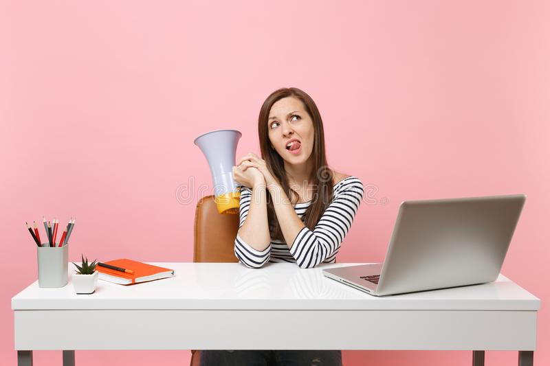 Puzzled doubting woman looking up showing tongue holding megaphone sit work at white desk at office with pc laptop stock photo