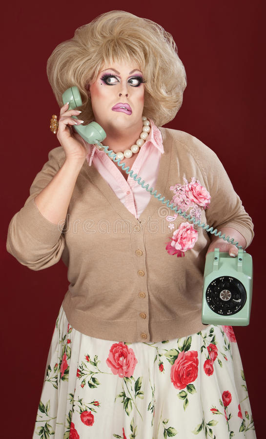 Puzzled Drag Queen. Confused drag queen on phone call over maroon background stock image