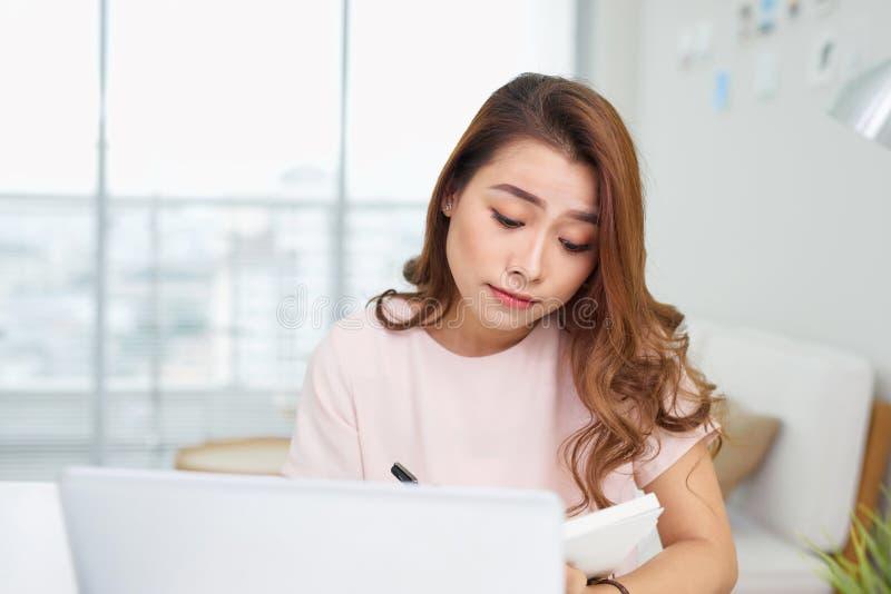 Puzzled förvirrad asiatkvinna som tänker hårt angånget om online-problemlösningen som ser bärbar datorskärmen, bekymrad allvarlig royaltyfria foton