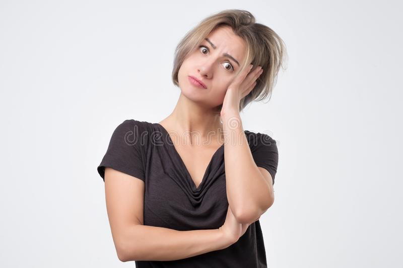 Puzzled female dressed in black t-shirt, being clueless and uncertain. royalty free stock photos