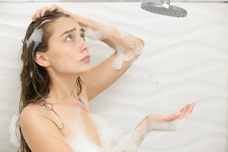 Puzzled foamed young woman. After the water in the shower was turned off, looking up at the shower. Lifestyle royalty free stock images