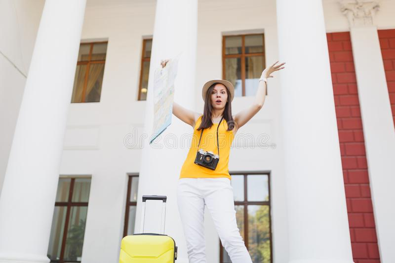 Puzzled irritated traveler tourist woman in hat with suitcase and retro vintage photo camera spreading hands hold city royalty free stock photo
