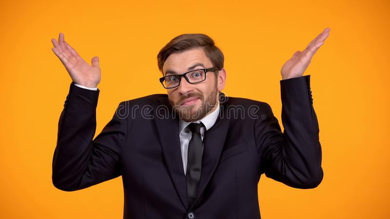 Puzzled man shrugging shoulders, looking confused, right to choose, options. Stock photo stock images