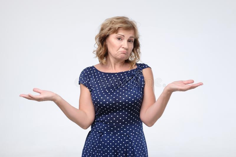 Puzzled mature female in blue dress shrugs shoulders as does not know answer stock photo