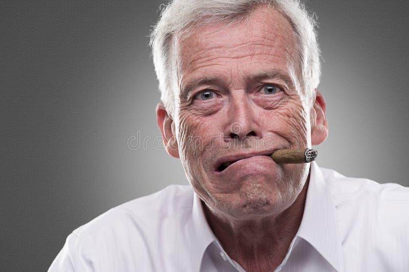 Puzzled senior man on gray background stock image