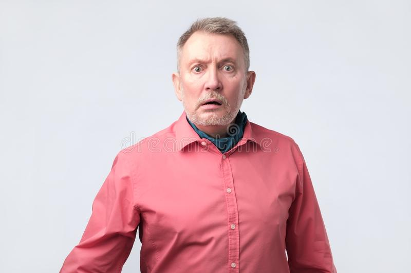Puzzled senior man has frustrated facial expression, frowns face in displeasure royalty free stock image