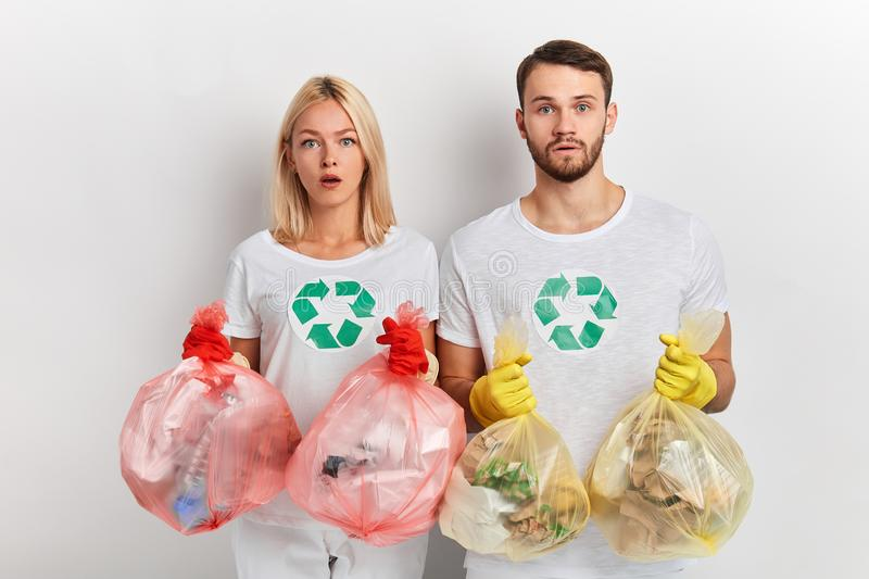Puzzled serious young people being worried with environmental problems. Puzzled serious young people being shocked with environmental problems. close up photo stock image