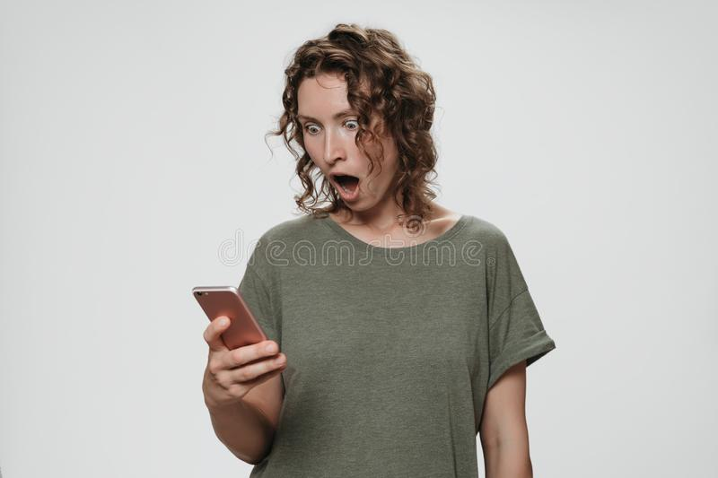 Puzzled stupefied curly hair woman opens eyes and mouth widely holding smartphone. Looks with terrified expression at screen reads with greate surprise shocking royalty free stock photo